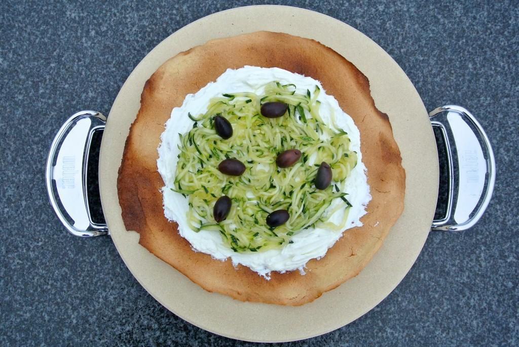 Socca schmeckt einfach so oder belegt: hier einfach und schnell mit Frischkäse, Zucchiniraspel und Kalamata Oliven